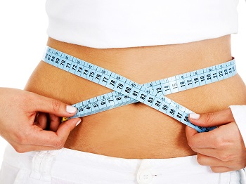 girl measuring her waist checking if she has had any weight loss - isolated over a white background